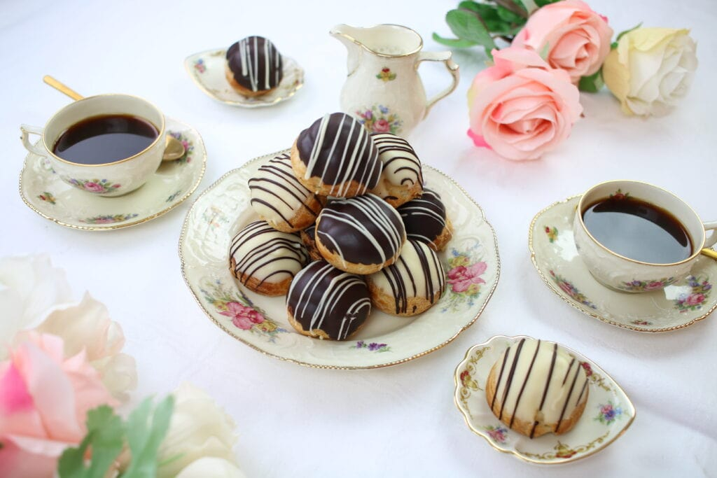 Cream puffs, a table is sett for two people to enjoy custard filled cream puffs and coffee