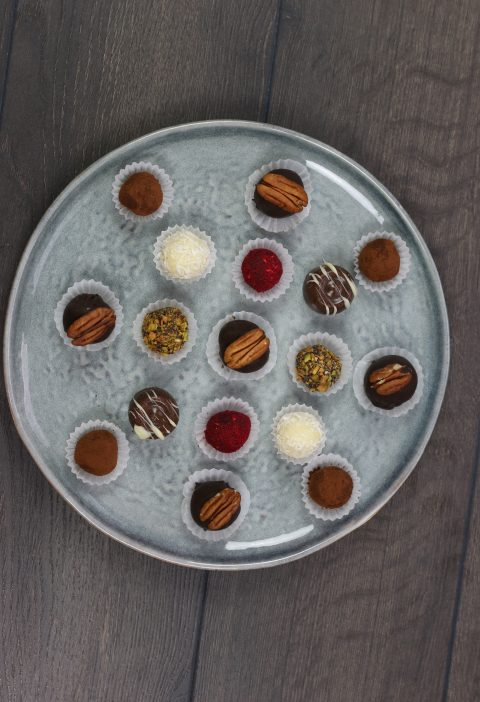 a grey plate with different chocolate truffles