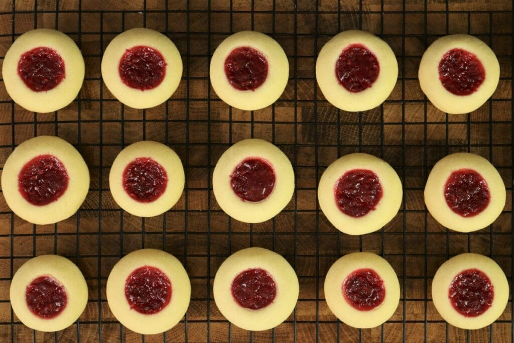 Thumbprint Cookies Filled With Raspberry Jam on a cooling rack