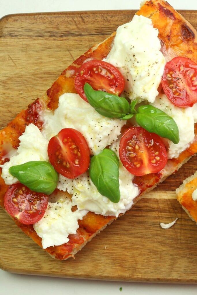 Pizza slice with Buffalo mozzarella fresh tomatoes and basil. Pizza al taglio recipe